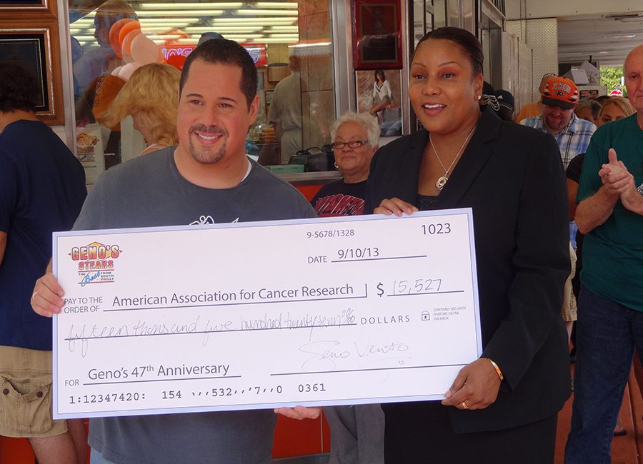 Geno, from Geno's Philly Cheesesteaks, presents a check